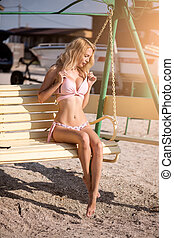 bonito, senta-se, jovem, balanço banco, menina, swimsuit, praia, arenoso