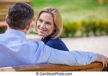 bonito, sentando, daydreaming, cada, meio, olhar, elegante, outro, adulto, bench., ao ar livre, sorrindo, idade, par