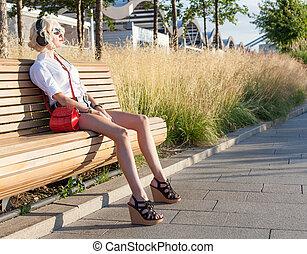 bonito, verão, moda, sapatos, sentando, shorts brim, banco, shortinho, pôr do sol, fones, menina, leggy, alto-colocar salto* no* sapato*