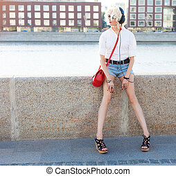 bonito, verão, moda, sapatos, sentando, shorts brim, shortinho, pôr do sol, fones, waterfront, menina, leggy, alto-colocar salto* no* sapato*