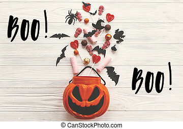 Boo! text sign. Happy Halloween. Jack o Lantern bucket with holiday candy, bats, spiders, skulls on white rustic wooden background. Season's greeting card. Trick or treat