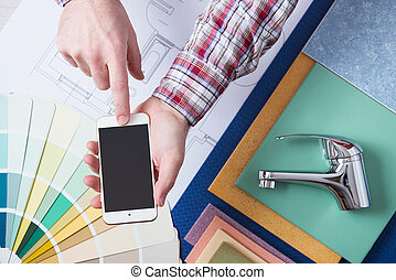 Book a plumber online - Male hands using a smart phone next...
