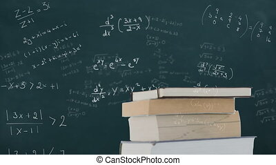 Book against mathematical equations on black board - ...