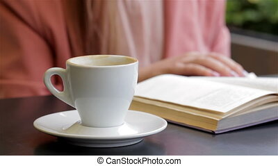 Book and a cup of coffee on the table