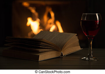Book and glass of wine in front of fireplace
