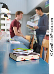 book and notepads on desk in library - closeup of closed...