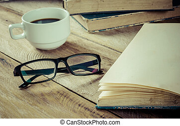 book eyeglass and cup of coffee on wood at morning