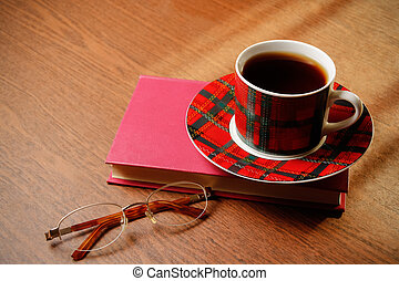 Book, glasses and tea on a wooden background
