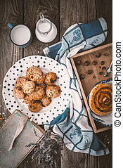 Book, lavender, oatmeal cookies and a cup of milk on old boards