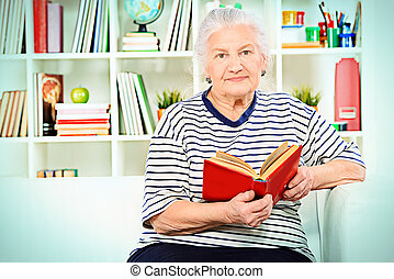 book of memories - Smiling senior woman sitting at home on a...