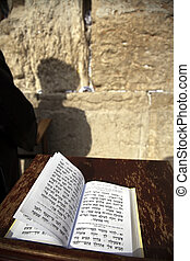 The biblical Book of Psalms opened on one of the pages of the morning prayer, resting on a pedistal . There's also a Jewish orthodox man infront of the wailing wall in the background, praying. Shot in the western wall in the old city of Jerusalem.
