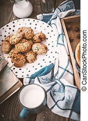 Book, pitcher, oatmeal cookies and a cup of milk on old boards