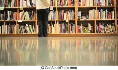 Book Shelves - People walking in front of stacks of books
