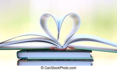 Book stack open page heart shape in wind, green garden...