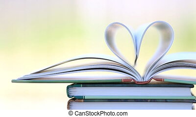 Book stack open page heart shape in wind, green garden...