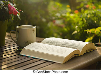 Book - Cup of tea and open book on wooden table in garden.