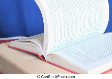 Book - The book rests on a wooden stand and a man leafing...