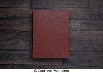Book, top view on wooden background, desk.