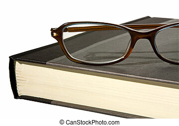 a close up partial view of a hardback book with a pair of reading glasses on top