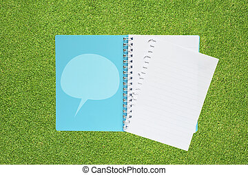 Book with comment on grass background