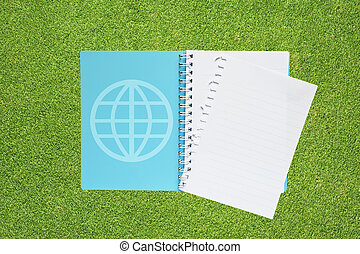 Book with global on grass background