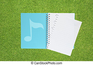 Book with music on grass background