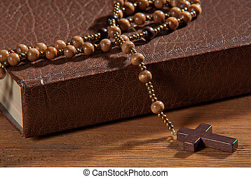 Book with rosary on the wooden table.