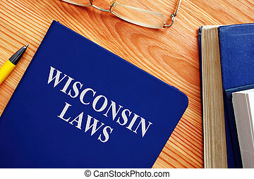 Book with State Wisconsin law on the wooden table.