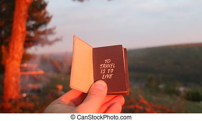 Book with the inscription to travel is to live. Sunset in the forest.