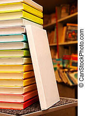 Book with white cover staying at stack of colorful books