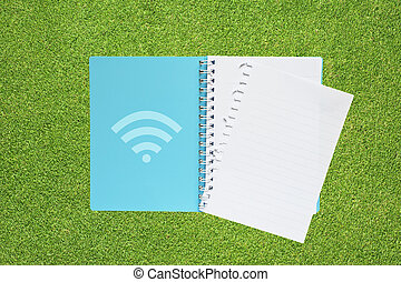 Book with wireless on grass background