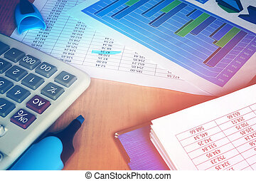 Calculator and financial figures on an office table.