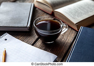 books and a cup of coffee on a wooden background