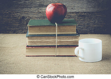 books and apple with coffee cup on retro background with...