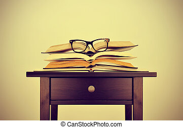 books and eyeglasses on a desk, with a retro effect - a pile...