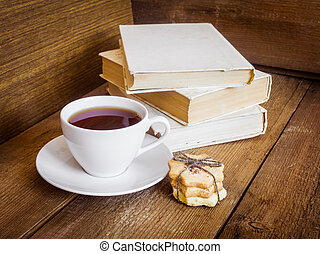 Books, cookies and cup of tea on wooden background
