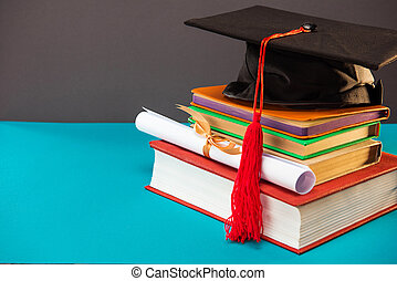 books, diploma and graduation cap with tassel on blue with copy space, education concept