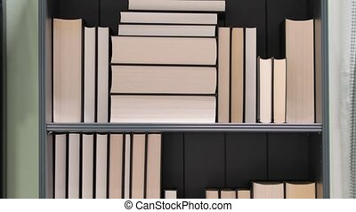 Bookshelf with series of books in piles and rows