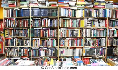 books on bookshelves and shopboard in bookshop, vertical...