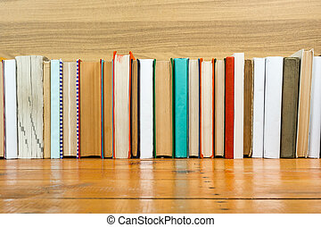 Books on grunge wooden table desk shelf in library. Back to school background with copy space for your ad text. Old hardback   no labels, blank spine