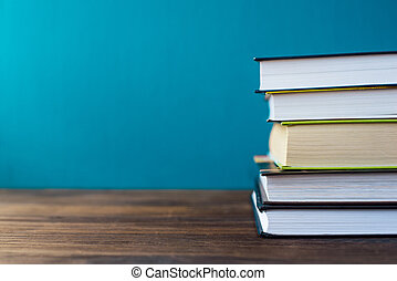 Books on table in front of chalk board.