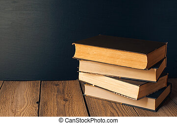 books stacked on a wooden table in a rustic style on the background a school blackboard. The concept of welcome back to school. copy space