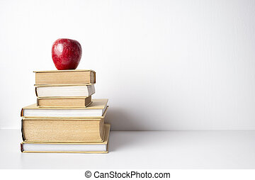 Books stuck with red apple with copy space, isolated on white background