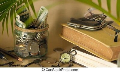 Books with glass penny jar filled with coins and banknotes....