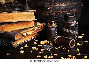 Books with spells, old pot, jars of potion are on a wooden dark table. Petals of dried roses are scattered nearby. Black background. Close-up shot.