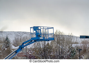 Boom lift against mountain and sky in winter