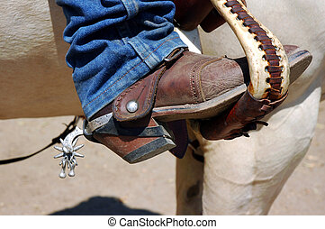 Western boot with old time spurs in stirrup.