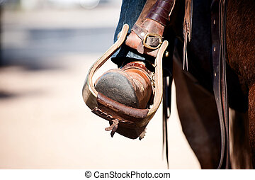 Cowboy leg and foot in stirrup on horse