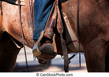 Cowboy's leg and foot in stirrup on horse