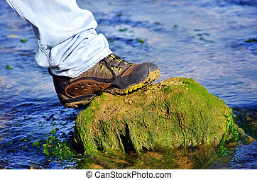 Boot on a rock in water of river